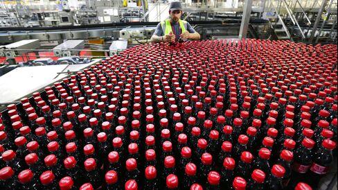 An employee inspects bottles at Coca-Cola Enterprises Ltd.'s bottling plant in Sidcup, U.K.