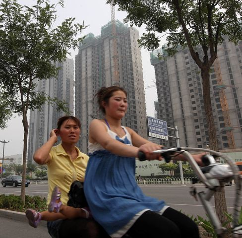 People ride past a construction site in Tianjin