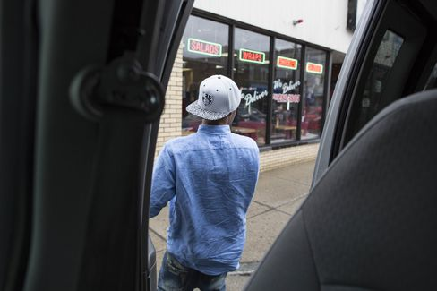 A young man from the Roca program is dropped off by case worker Sulai Rosa on Broadway, a popular hangout for Bloods and other gang members in Revere, Massachusetts, on April 15, 2014. Photographer: Scott Eisen/Bloomberg