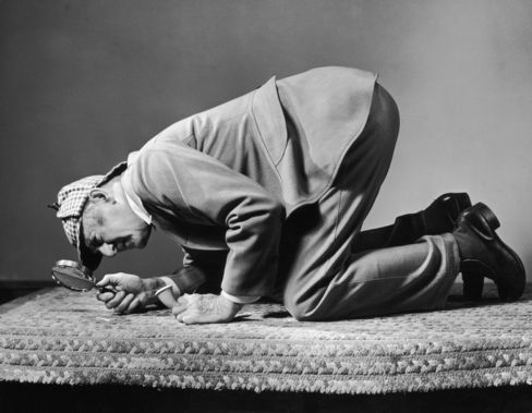 A man wearing a Sherlock Holmes costume inspects a carpet with a magnifying glass. Photographer: Harold M. Lambert/Lambert/Getty Images