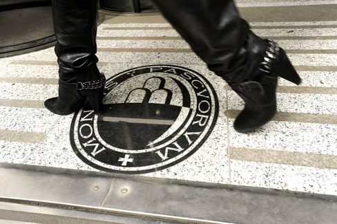 A woman walks over a Monte dei Paschi di Siena bank logo at one of the bank's branches in Milan, Italy. Photographer: Giuseppe Aresu/Bloomberg