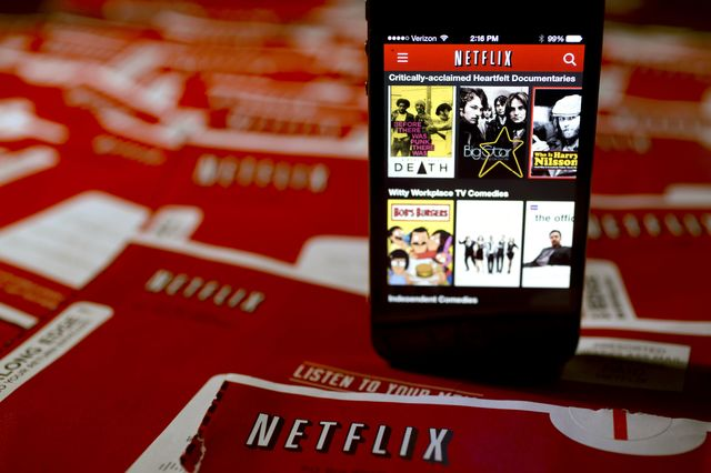 As Comcast builds a moat around its subscribers, Netflix is paying to get in. Photographer: Andrew Harrer/Bloomberg
