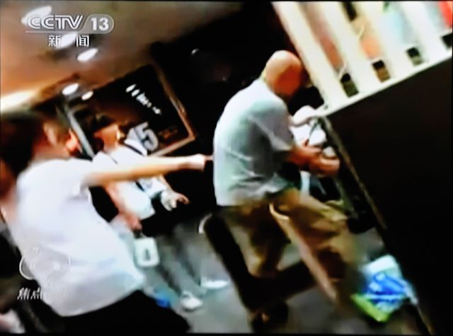 In this screen shot of a surveillance video, women reportedly ordered Zhang Lidong, right, to kill a woman at a McDonald's restaurant in  Shandong province.