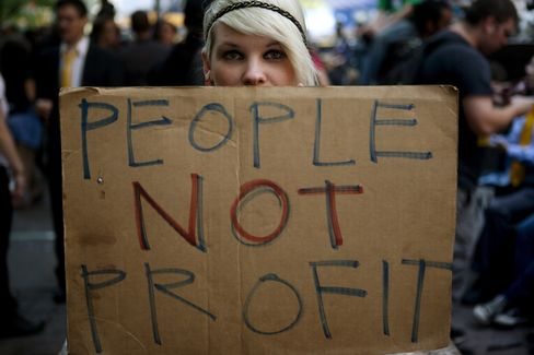 An Occupy Wall Street protestor holds a sign during a demonstration in New York in 2012. Photograph by0xA0Victor J. Blue/Bloomberg