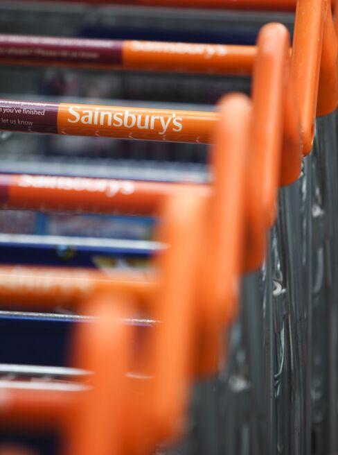 Shopping Carts Sit Outside A Sainsbury's Supermarket