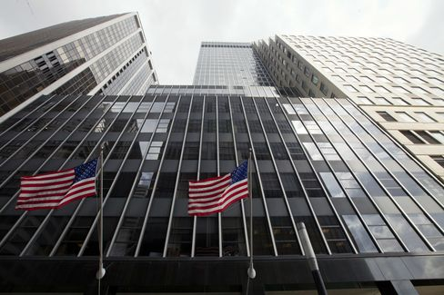 Flags fly outside the building located 110 Wall Street in New York. Photographer: Jin Lee/Bloomberg