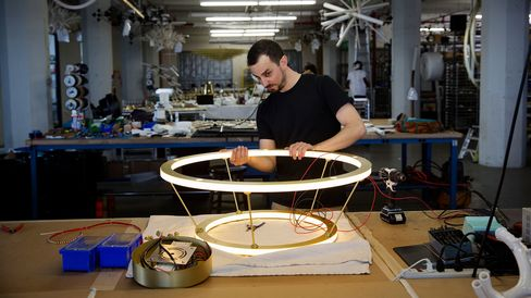A worker builds a light fixture at the Roll & Hill manufacturing facility at Industry City in the Brooklyn borough of New York, on July 2, 2015. Photographer: Victor J. Blue/Bloomberg