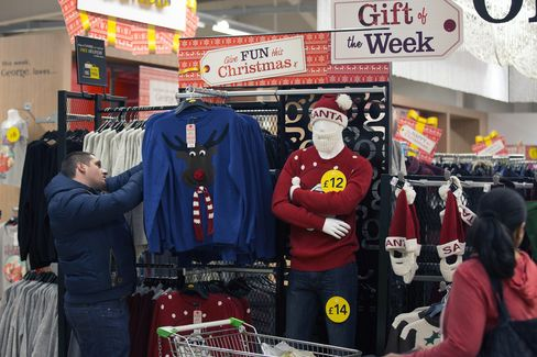 A Customer Looks at Jumpers for Sale in a Store in London