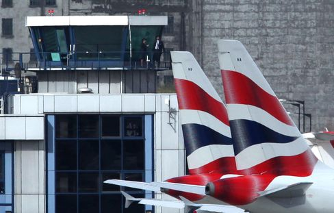 Air traffic control employees look out from the control tower at grounded British Airways airplanes at City Airpo