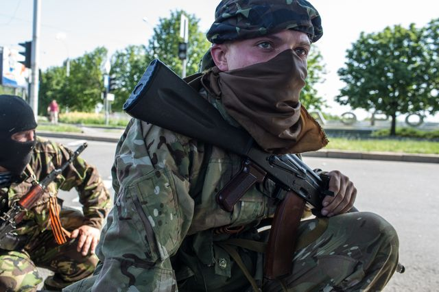 Pro-Russian separatist fighters take positions outside the Donetsk airport Monday. Photographer: Brendan Hoffman/Getty Images