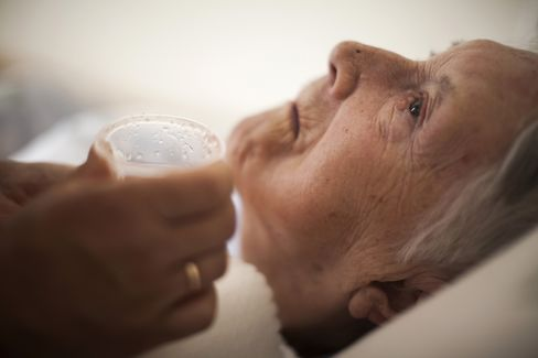 Sonja Miskulin, a German pensioner, rests on her bed after celebrating her 94th birthday at the Polish care home for the elderly where she lives in Szklarska Poreba, Poland, on Aug. 24, 2013. Photographer: Bartek Sadowski/Bloomberg