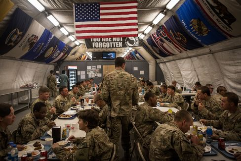 Soldiers in the U.S. Army eat dinner at Forward Operating Base Azzizulah in Kandahar Province, Maiwand District, Afghanistan on March 18, 2013. Photographer: Andrew Burton/Getty Images