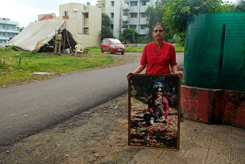 Ayesha Masood, the sister of Shehla Masood, poses with a photograph of her sister, while standing at the location of her sister's killing in Bhopal, India. Photographer: Gethin Chamberlain via Bloomberg