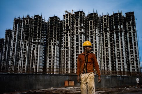 A construction worker stands on the site of a housing block in Sector 105 of Noida, in Uttar Pradesh, India. Growth in India is approaching its weakest pace in three years. Photographer: Sanjit Das/Bloomberg
