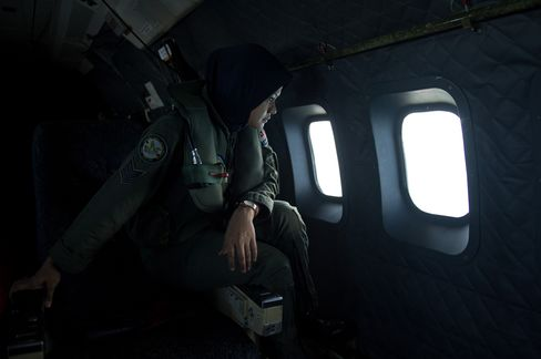 A crew member looks out the windows of a Malaysian Air Force aircraft during a search operation to find the missing Malaysian Airline System Bhd. jet, on March 15, 2014. Photographer: Mohd Rasfan/AFP via Getty Images
