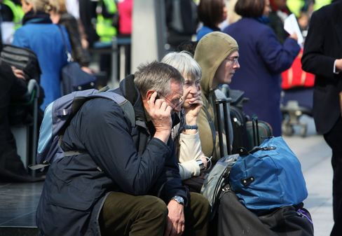 Passengers wait outside Terminal 3 at Heathrow Airport