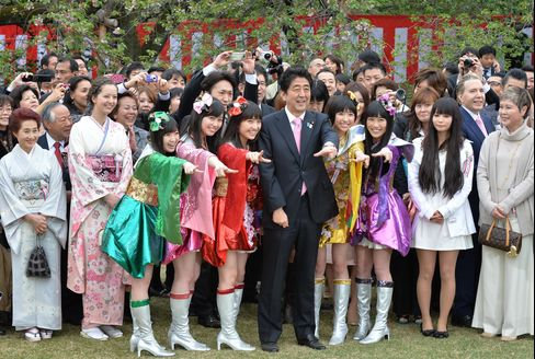Shinzo Abe, Japan's prime minister, center, poses for photographs with guests and performers during a garden party to admire cherry blossoms hosted by Abe at Shinjuku Gyoen park in Tokyo on April 20, 2013. Photographer: Kazuhiro Nogi/AFP via Getty Images