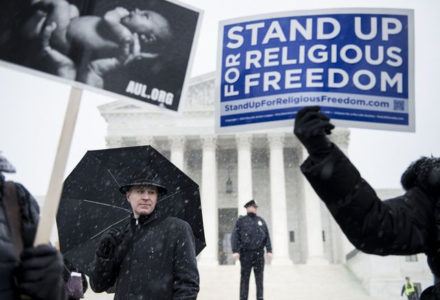 People who support Hobby Lobby's choice to withhold contraceptive healthcare coverage from their employees rally outside the U.S. Supreme Court on March 25.Photographer: Brendan Smialowski/AFP/Getty Images