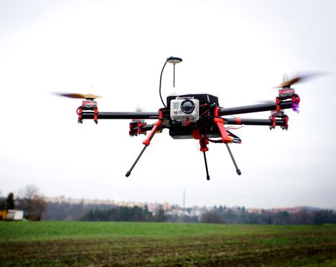 A SteadiDrone QU4D Quadrocopter carries a GoPro Hero 2 camera unit as it hovers during a test flight outside the headquarters of Mensuro Ltd., a distributor for SteadiDrone Ltd. products, on Dec. 10, 2013. Photographer: Martin Divisek/Bloomberg