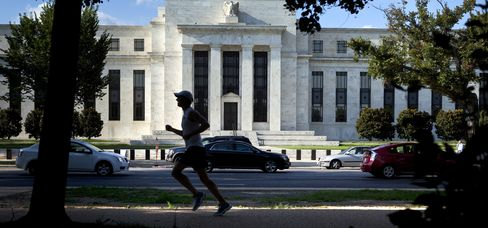 A jogger passes in front of the U.S. Federal Reserve building in Washington, D.C., U.S. Photographer: Brendan Smialowski/Bloomberg