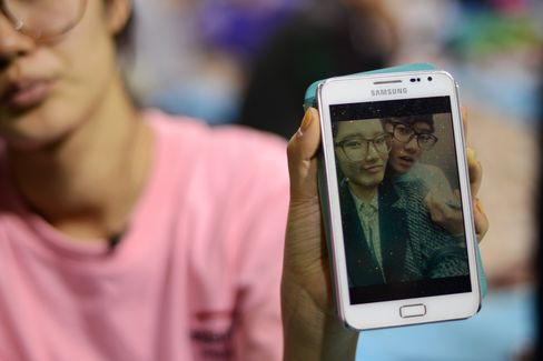 Hana Kim shows a photo of her brother Kim Dong Hyup, who is missing after the sinking of a South Korean ferry, as she sits in a gymnasium used as a gathering point for family members of missing passengers, on April 19, 2014. Photographer: Ed Jones/AFP via Getty Images