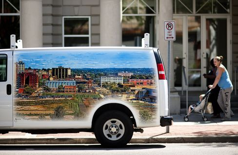 Pedestrians walk by a van with a painted