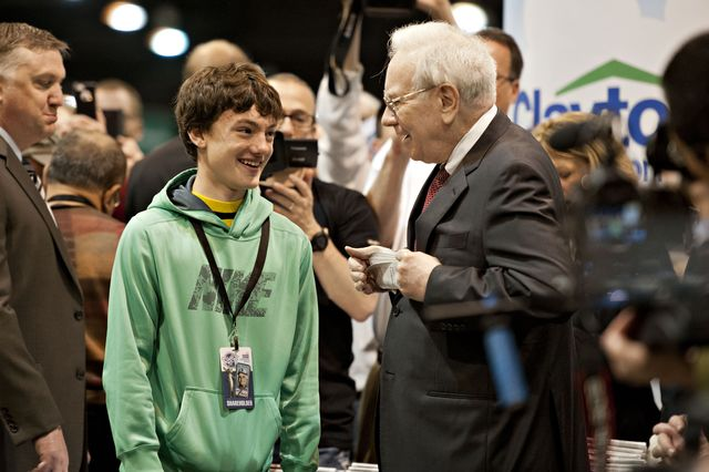 Warren Buffett talks to a young attendee at Berkshire Hathaway's annual meeting. Photographer: Daniel Acker/Bloomberg