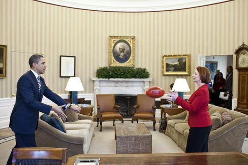 U.S. President Barack Obama practices passing an Australian football with Prime Minister Julia Gillard of Australia in the Oval Office of the White House in Washington, on March 7, 2011. Photographer: Pete Souza/White House