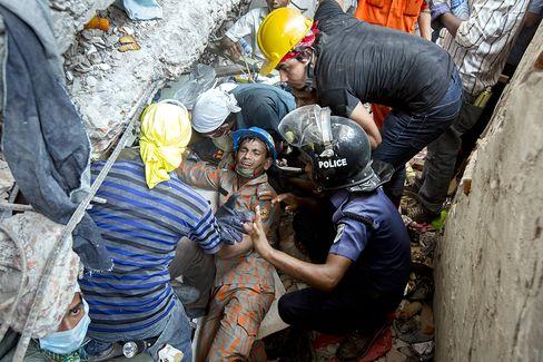 Rescue workers and volunteers search by hand for victims amongst the debris of the collapsed Rana Plaza building in Dhaka, Bangladesh, on April 26, 2013. Photographer: Jeff Holt/Bloo