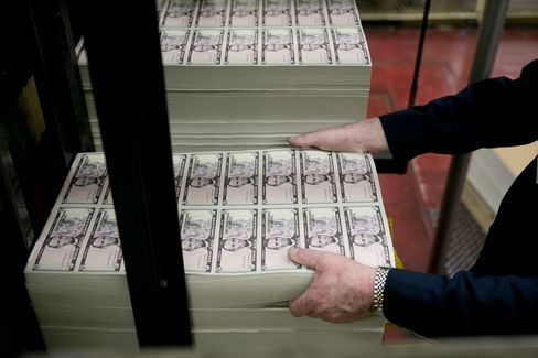 An employee loads a machine at the Bureau of Engraving and Printing. Photograph by Andrew Harrer/Bloomberg