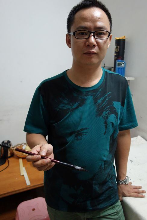 He Junfeng, a migrant worker, holds a calligraphy brush in Guangzhou, China. Source: Bloomberg