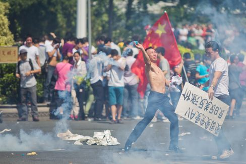 An anti-Japanese protester throws a gas cannister during a demonstration over the disputed Diaoyu Islands in Shenzhen, China. Photographer: Lam Yik Fei/Getty Images