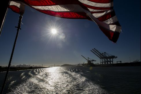 A U.S. Flag Flies as Cranes Stand at the Port of Oakland