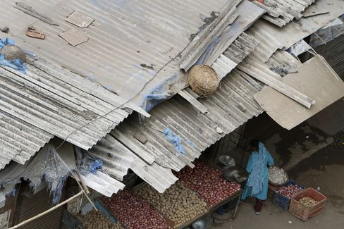 A woman stands at a vegetable stall in a slum dwelling with asbestos rooftops in Mumbai, India. Photographer: Adeel Halim/Bloomberg