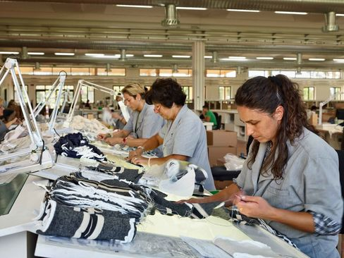 Workers at a Cucinelli factory in Solomeo inspect cashmere for defects.