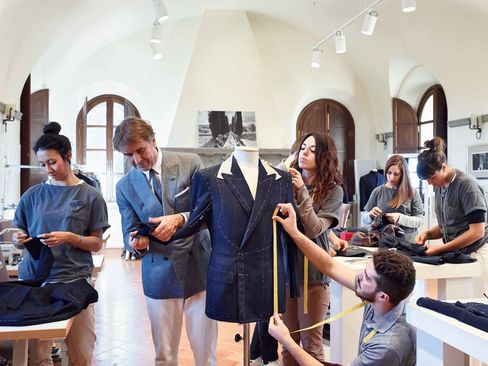 Brunello Cucinelli works with tailoring students at the School of Craftsmanship he started in Solomeo, Italy.