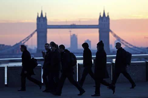 Commuters walk across the River Thames on London Bridge, past Tower Bridge, in London. Photographer: Chris Ratcliffe/Bloomberg