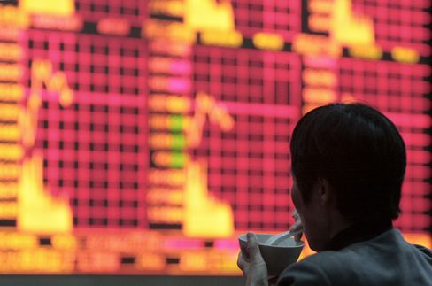 An investor monitors stock boards in Shanghai