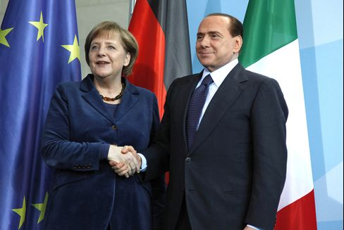 German chancellor Angela Merkel, left, greets Prime Minister Silvio Berlusconi, at the German Federal Chancellory in Berlin. Photographer: Jochen Eckel/Bloomberg
