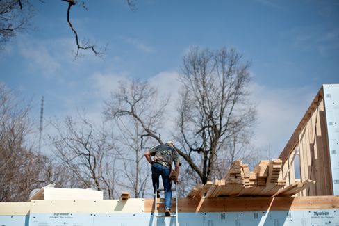 A worker climbs a ladder to the second floor of a single family home being built in East Peoria, Illinois. Photographer: Daniel Acker/Bloomberg