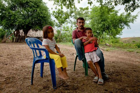Javier Diaz, with his children at his stepfather's house near Sincelejo, says he will file a claim to win back the land he sold after receiving death threats. Photographer: Andre Vieira/ Bloomberg Markets via Bloomberg.