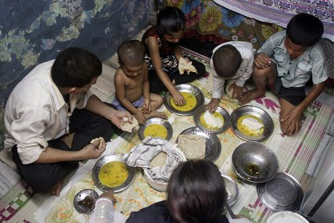 Hafiz Khan, left, eats lunch along with his wife, middle bottom, and four children in their rented home in the Dharavi slum area of Mumbai, India. Photographer: Dhiraj Singh/Bloomberg