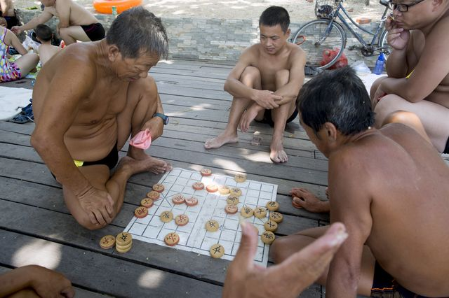 Playing Chinese chess at the beach in a Speedo is OK. Photographer: Brent Lewin/Bloomberg