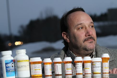 Mikel Hehn poses in St. Cloud, Minnesota, with the daily medications he takes to combat pain and depression as a result of his spinal surgery. Photographer: Andy King/Bloomberg