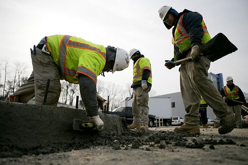 Contractors smooth the concrete on a curb at Skanska USA Building Inc.'s's Inova Health System construction site in Lorton, Virginia. Photographer: Andrew Harrer/Bloomberg