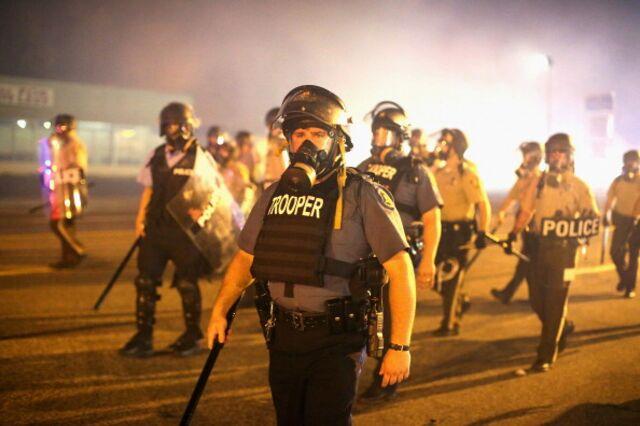 Police advance through a cloud of tear gas toward demonstrators protesting the killing of Michael Brown on Sunday inFerguson, Missouri.