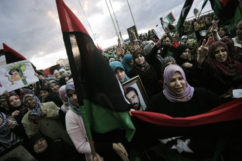 People holding old national flag shout slogans in Benghazi