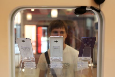 A Customer Inspects a Display of Smartphones in a MTS Store