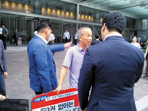 Hwang Sang-ki (center) confronted by Samsung security.
