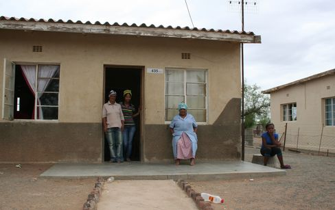 Eva Matthys sits in front of her government-subsidized house, with granddaughters, right, and center left, and cousin Anneline Maarman, in Brandvlei. Photographer: Rene Vollgraaff/Bloomberg
